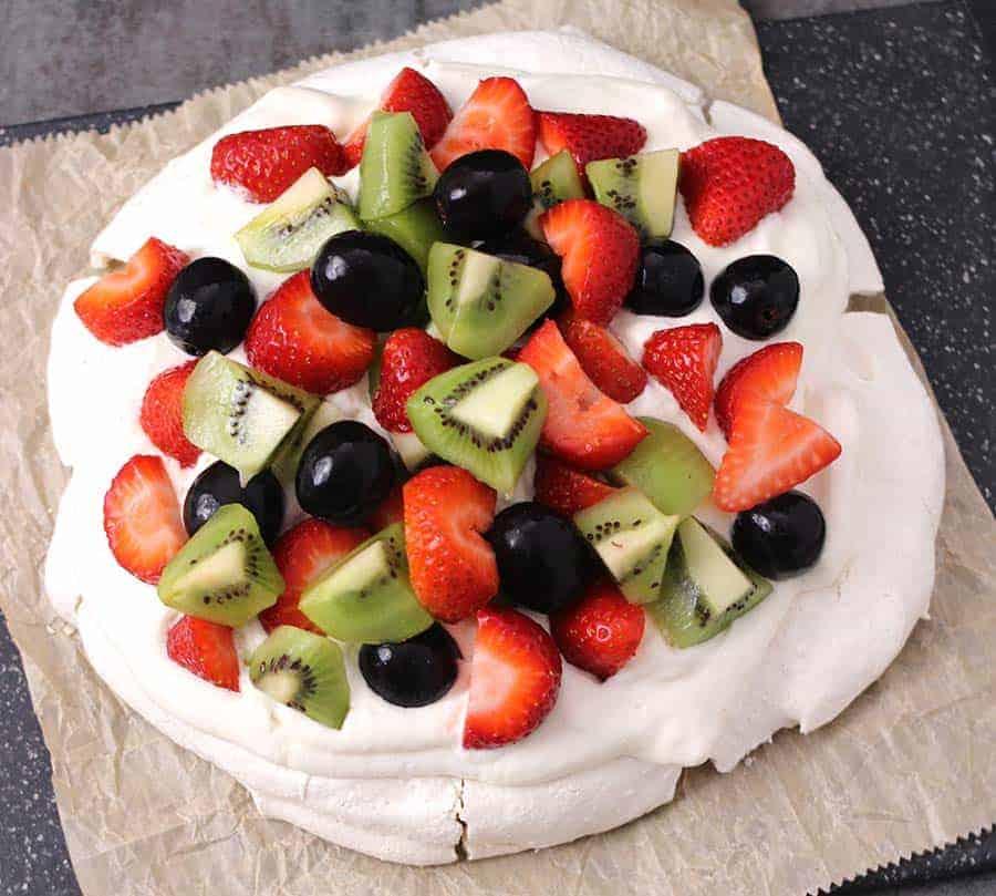 Pavlova - meringue based gluten free cake dessert topped with fresh fruits and homemade whipped cream.